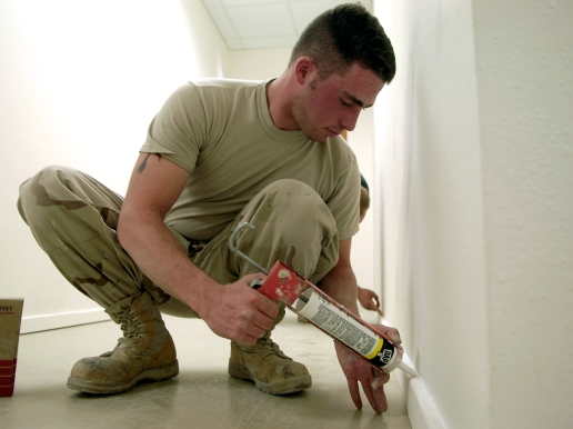 Senior Airman Collin Uvanni caulks the baseboards of the new post office at Bagram Air Base, Afghanistan, on Tuesday, June 6, 2006. The office, constructed entirely by the 1st Expeditionary Red Horse Group, will nearly double the size of the existing post office. (U.S. Air Force photo/Senior Airman Brian Ferguson)